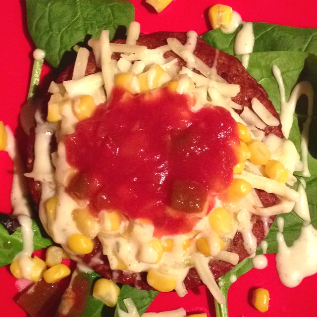 Spicy Black bean burger on a bed of spinach. Topped with pepper jack ...