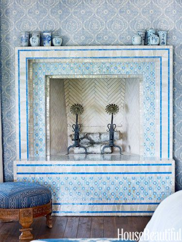 A fireplace in blue Moroccan tile against exotic wallpaper. Design: Martin Horner
