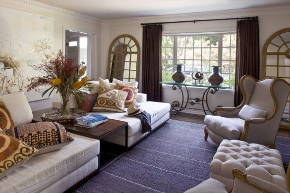 Layered living room with leaning wall mirrors, wingback chairs, and ethnic textile throw pillows