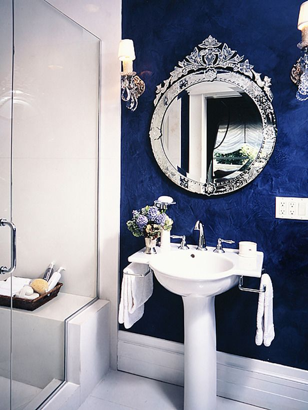 Designer's Notes  A striking color combination of white and royal blue gives this bathroom style. The simple floor and bath surround harmonize with the antique Venetian mirror and antique sconces. Blue Venetian plaster adds luxury. Tip: Don't be afraid to mix a modern sink and hardware with an antique mirror.