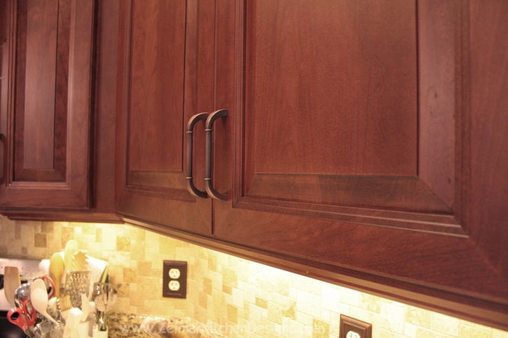 cherry cabinets with LED cabinet lighting and decorative hardware
