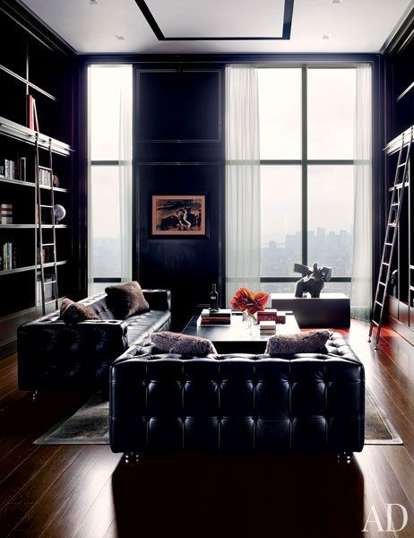 The dark-walled library of a New York penthouse features tufted-leather sofas.