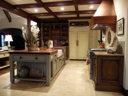 "The cabinets were custom made in England, painted with Farrow & Ball's French Gray, and glazed. Natural pine base cabinets flanking the range are also glazed, and topped by honed Golden Leaf granite. Panels on the 48"" GE Monogram fridge are painted with Farrow's Cream and glazed as well."
