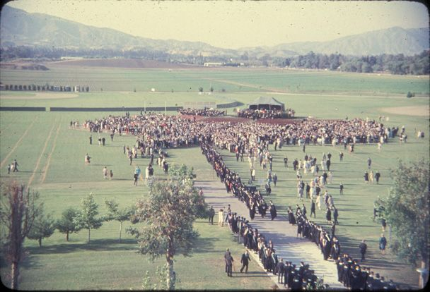 This is an image of the first graduation at San Fernando Valley State College (SFVSC, now CSUN) in June of 1959. Ninety students received their degrees on the SFVSC football field. This image shows the large expanse of empty land held by the college at this time; visible in the background is the Santa Susana mountain range. CSUN University Digital Archives.