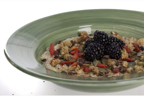 Steel cut oats topped with dark chia seeds, goji berries, flax seeds ...