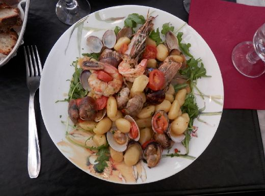 ... with shrimp, clams, tomatoes and arugula in a garlic wine sauce