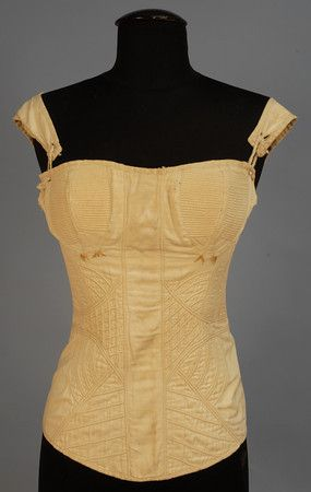 WHITE COTTON CORSET, c. 1820. Hand quilted, having channel in front for busk, no stays, decorative ivory embroidery beneath cups, eyelets in back, tab straps attached with string. Bust 26, waist 21, length 21. (No laces) excellent. $1,380.00