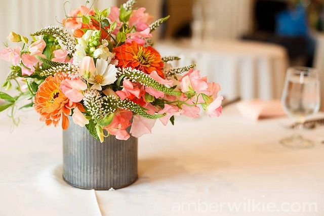 Peach, coral and pink tones with splashes of white and green in a rustic metal can.