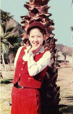 赤いスカートにベストを着てヤシの木の前に立つひし美ゆり子の画像
