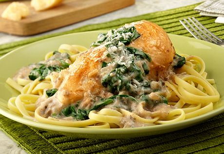 Tender, boneless chicken breasts are topped with a savory mixture ...