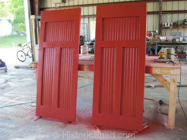 Red craftsman style front door features leaded glass sidelights