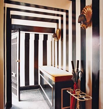 Entry for the gentleman - black and cream striped walls, brass shell sconces with black shades, bench and iron umbrella stand