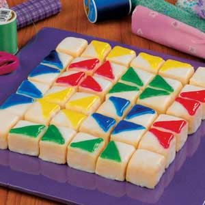 """Petit Four Quilt Recipe      FOR your next quilting bee, crafty gathering or any time at all, serving up this dessert will ensure your occasion's a real blockbuster! To piece together these delectable petit fours, simply cut a purchased pound cake into cubes and cover them with a citrus-flavored glaze. Then blanket the goodies with decorating gel in a colorful Dutchman's Puzzle design. Follow the easy """"pattern"""" here, and you'll sew up treats in not time!"""