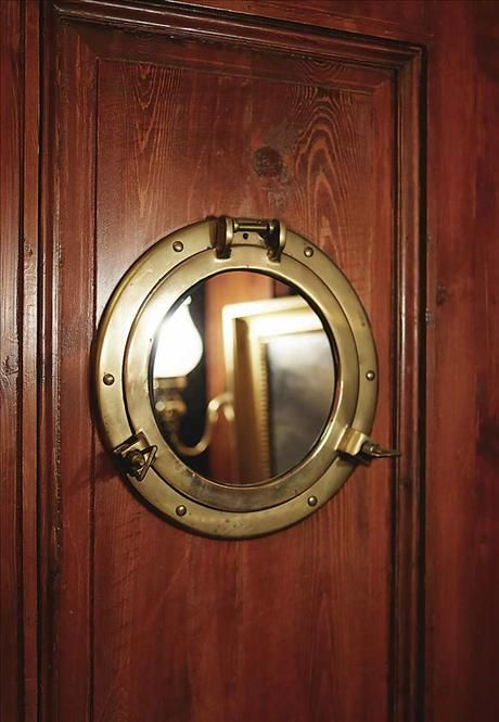Brass porthole mirror provides more visual space