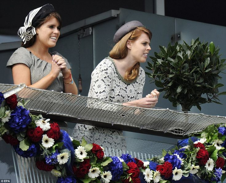 Enjoying the races: Princess Eugenie of York, left, and Princess Beatrice of York, right, eagerly lean over the rails of the Queen's balcony to watch the races