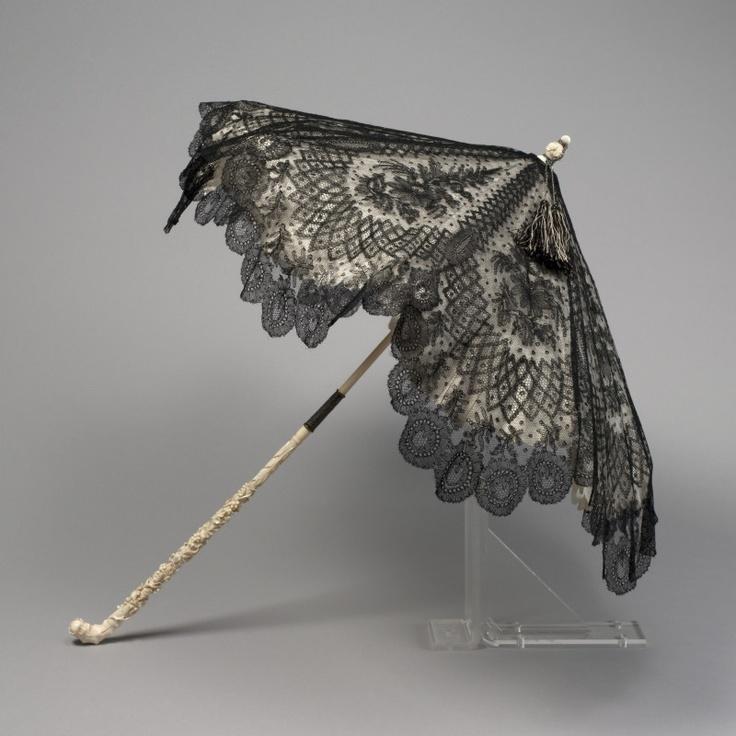 """Poulain Ombrelle marquise, vers 1860 Couverture en dentelle de Chantilly noire, doublure en taffetas ivoire dentelé à l'emportepièce, carcasse en fanon de baleine, mât, embout et poignée en ivoire sculpté, coulant en métal, cordelière et glands de soie noire et blanche. Griffe sur le coulant : """"POULAIN / BOULEVARD DE LA MADELEINE, 3 / PARIS"""" Paris, Galliera - musée de la Mode de la Ville de Paris © Stéphane Piera / Galliera / Roger-Viollet"""