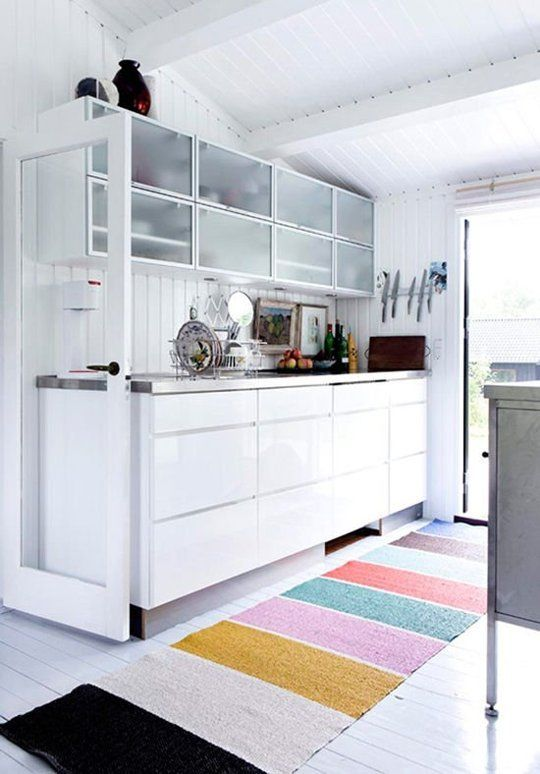 a gorgeous white modern kitchen is saved from boring with a colorful striped floor rug