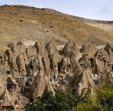 "Iranian Troglodyte Homes~The Iranian village of Kandovan is usually described as a ""gigantic termite colony"". Volcanic rock formed a small group of cone-like caves that eventually attracted human inhabitants. The small town, like many of the other underground dwellings on this list, has become a veritable tourist destination."