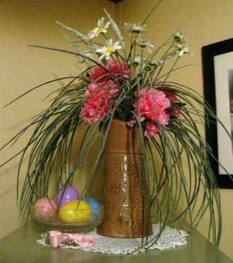 More Easter around the house. Just stuck some pink flowers in an existing planter. Then I put a few Easter eggs in a candy dish and tied a pretty pink ribbon around the base.