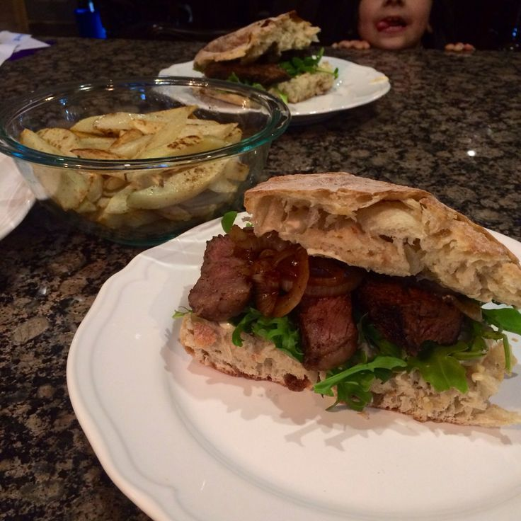 ... Steak Sliced on a chiabata bread with baby arugula and sautéed onions