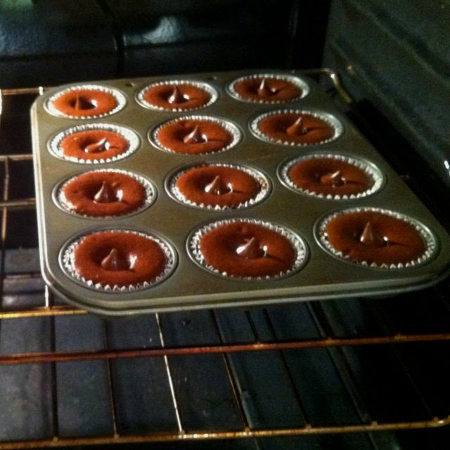 Bake cupcakes for 5 minutes and then drop a Hershey Kiss in the center and continue baking. It sinks to the middle and makes a chocolate center