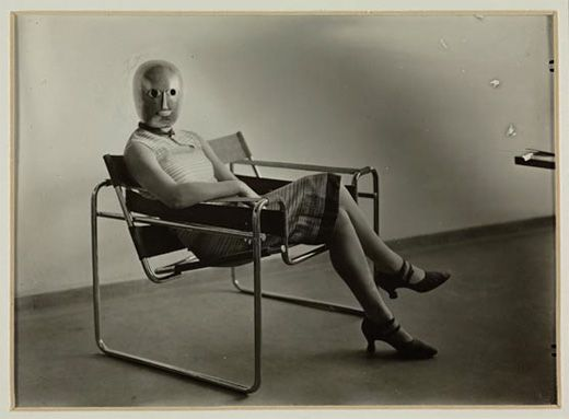 Lis Beyer or Ise Gropius sitting on the B3 club chair by Marcel Breuer and wearing a mask by Oskar Schlemmer and dress fabric by Beyer, c.1927. Herzogenrath, Berlin