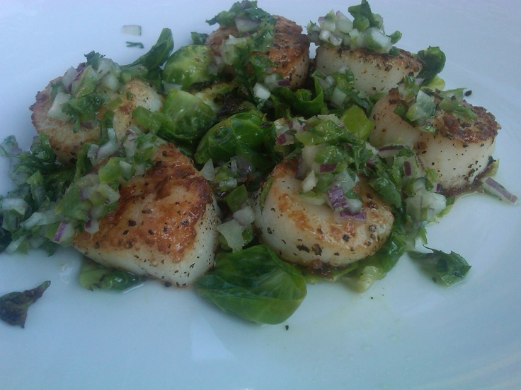 Seared sea scallops with sauteed brussel sprouts leafs topped with a ...