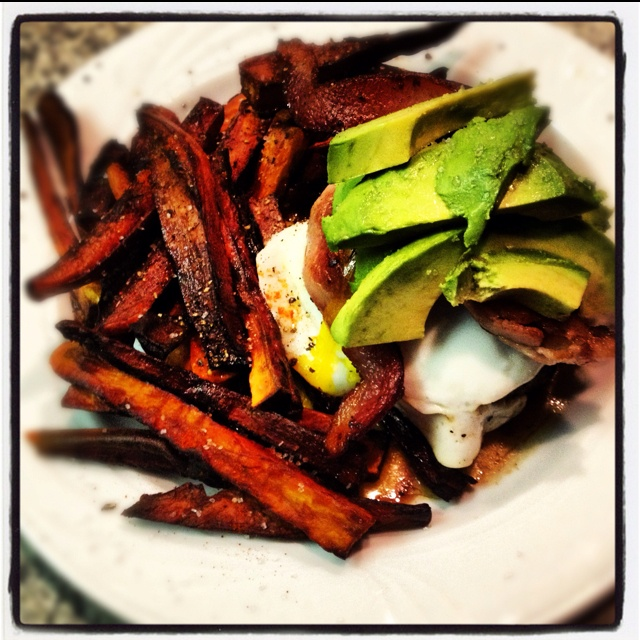 Bun-less bison burger topped with avocado, bacon and fried egg. Side ...