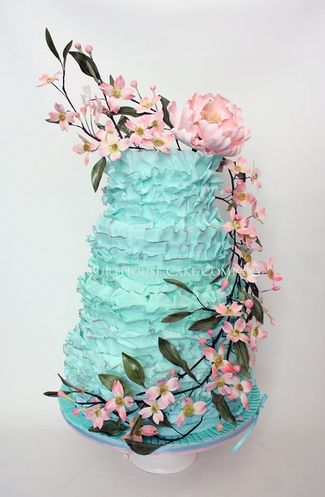 An unusual and striking blue vintage ruffle wedding cake with a pink peony added to the trailing pink Dogwoods.