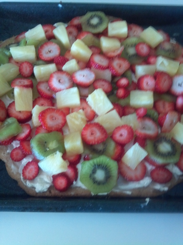 FRUIT PIZZA -Form a large cookie out of sugar cookie dough and bake on cookie sheet. (350 15 mins or more if needed). Take out of oven and spread with cream cheese. Slice fruit pieces (strawberries, kiwi, pineapple) and place on top. Cover and place in frig to cool. Take out and cut in slices with pizza cutter and serve! Enjoy! Healthy and delicious.  One of our favorite dishes  at the beach or anytime!