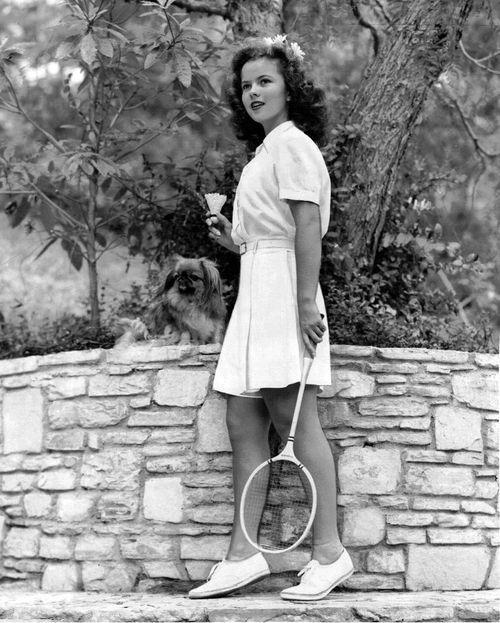Shirley Temple profiter d'un jeu de badminton (comme un petit pékinois chéri chiot regarde). # Vintage # 1940 # actrices # # badminton sport