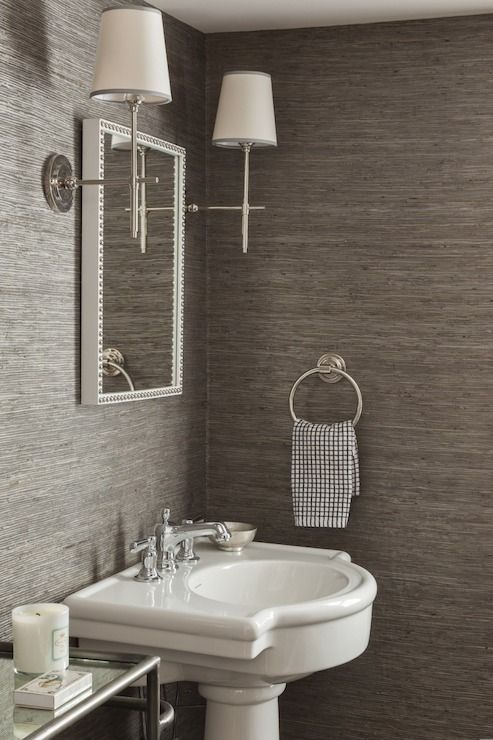 Chic powder room features walls clad in gray grasscloth wallpaper ...