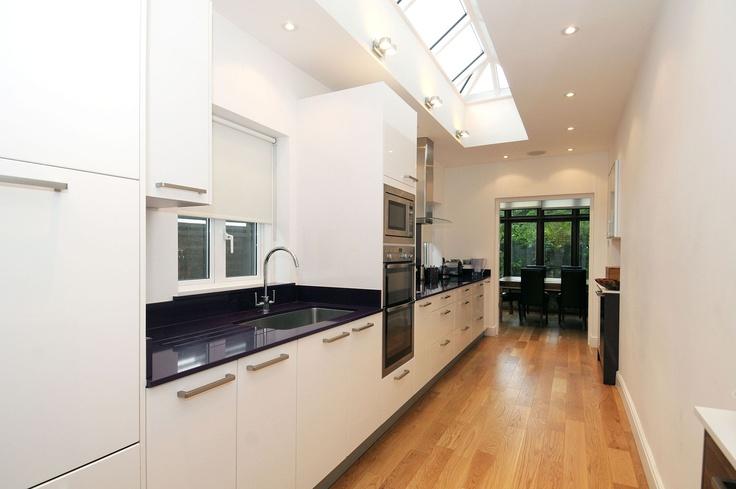 Cocina alargada, con toda la superficie de trabajo y almacenamiento a un lado. Separa la zona de cocción y de aguas poniendo la columna de hornos en medio.