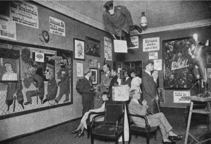 First International Dada Fair, Berlin, June 30, 1920, Hannah Höch (seated at left), George Grosz (in hat, standing, to right), and Grosz's Germany: A Winter's Tale (behind on right wall)