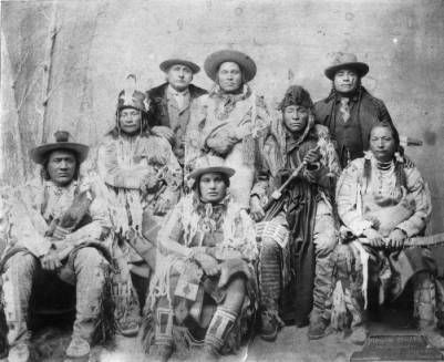 Blackfeet Chiefs, 1882  top row from left to right: Running Crane, White Grass, Tail Feather, Coming Over the Hill, and Young Bear Chief. Bottom row: Four Horses, Little Dog, White Calf, and Little Plume. Several men wear wide brim hats, two wear fur hats. Two men wear suits, vests and ties; other clothing includes beaded and fringed buckskin shirts and leggings. Two hold tomahawks, one holds a club.