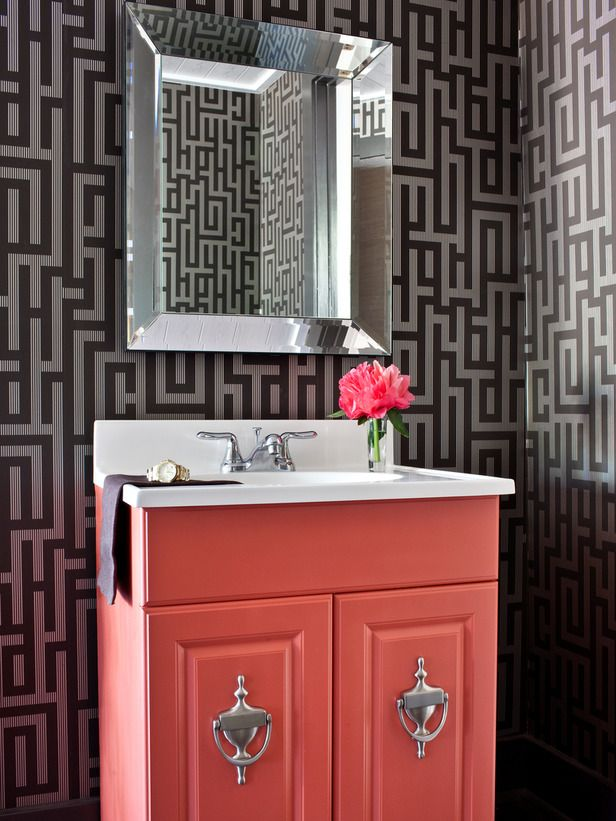Love the wallpaper. The coral vanity brings high-contrast charm to this small bathroom.