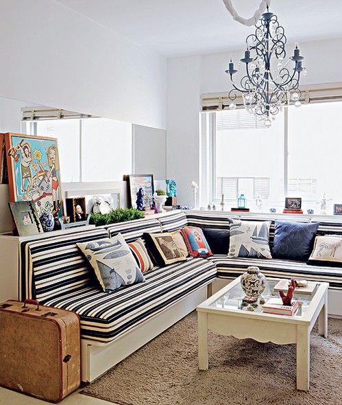 """O apartamento de 45 m² tem sala com estilo navy. O sofá em """"L"""" vira duas camas de solteiro para visitas. Uma faixa horizontal de espelho atrás dele parece alongar o espaço pequeno, que ganha outra """"janela"""". Projeto do arquiteto Marco Antonio Medeiros"""