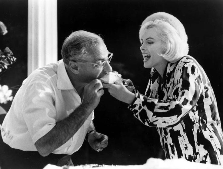 "Director George Cukor gets a bite of Marilyn Monroe's cake on the set of the ill-fated ""Something's Got to Give"" 1962"