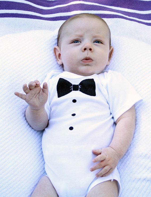 Baby boys tuxedo style bodysuit by The Tiny Universe, a Swedish designer renowned for its clean lines. It is made in soft and stretchy cotton jersey with white cotton pleat detail on the front and a .