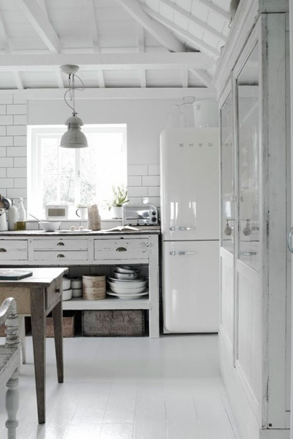 All white kitchen with worn open shelving and white painted wood ...