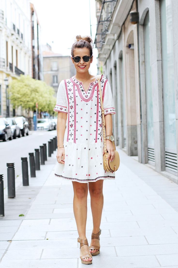 Brightly, delightfully embellished white tunic dress with pale leather shoes and bag.