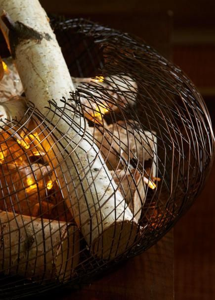 No fireplace for that cozy fall feel? Fill a large bowl or wire basket with logs. Weave in battery-powered orange twinkle lights and enjoy the glow. More fall decorating ideas: http://www.midwestliving.com/homes/seasonal-decorating/easy-fall-decorating-projects/page/49/0