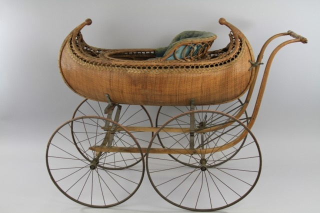 "VICTORIAN CANOE FIGURAL BABY'S CARRIAGE  Very rare example, reed and wood slat, shaped with ornate finials, canoe design body, large spoke wheels, a truly luxury early pram, with all wood handles, plush interior done in blue upholstery. 48"" w x 40"" h."
