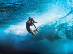 Female surfer beneath the waves