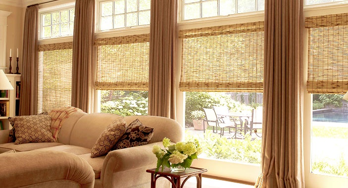 Natural roman shades flanked by curtains