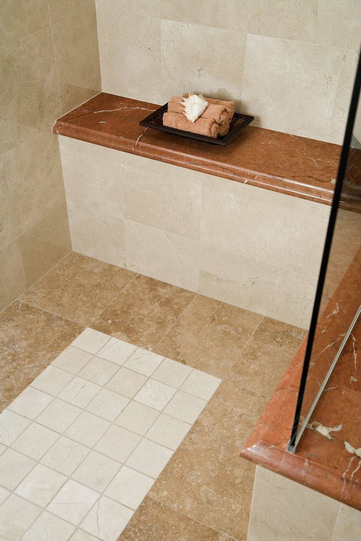 traditional shower with tile all around and a granite seat in back
