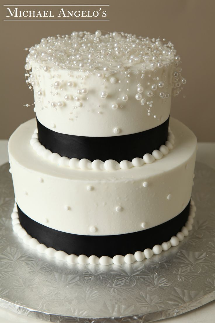 black satin ribbon surrounding the layers and a pearl mesh topper to ...