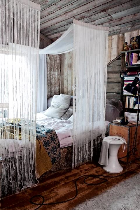 This bohemian style bedroom is perfection paired with deep hardwood floors and bleached wooden walls.