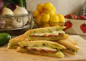 Panini with caramelized onions, tomato, pesto and mozzarella
