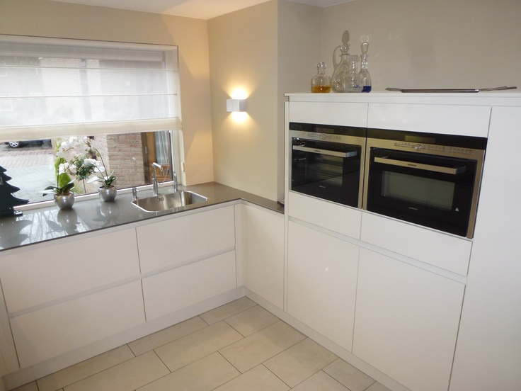 Volledig witte greeploze L keuken met halfhoge kasten en